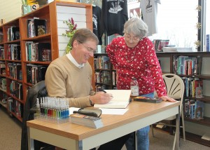 John Benedict signs a copy of Fatal Complications for a fan